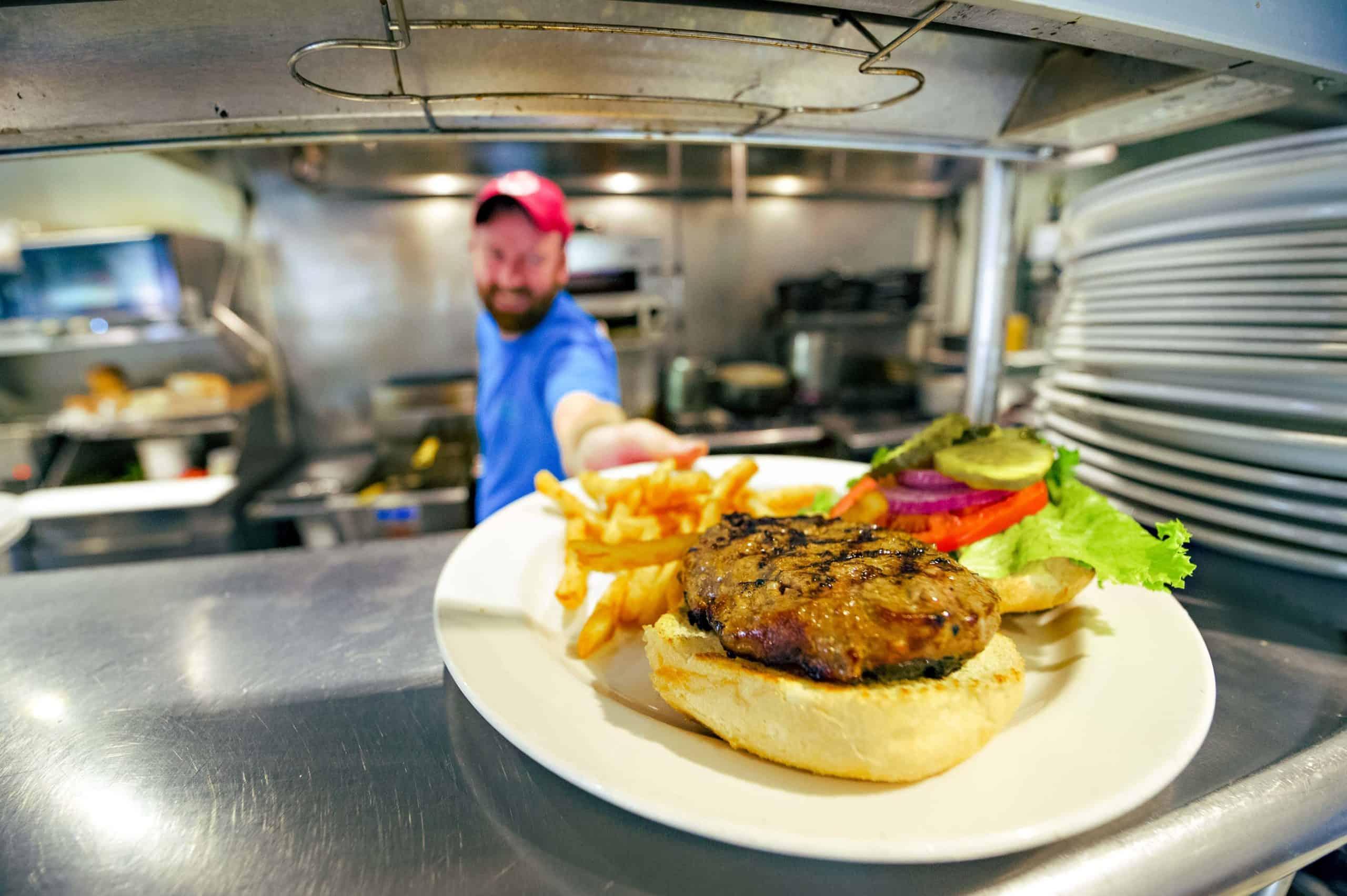 Man serves a burger from the kitchen of Café Alfresco